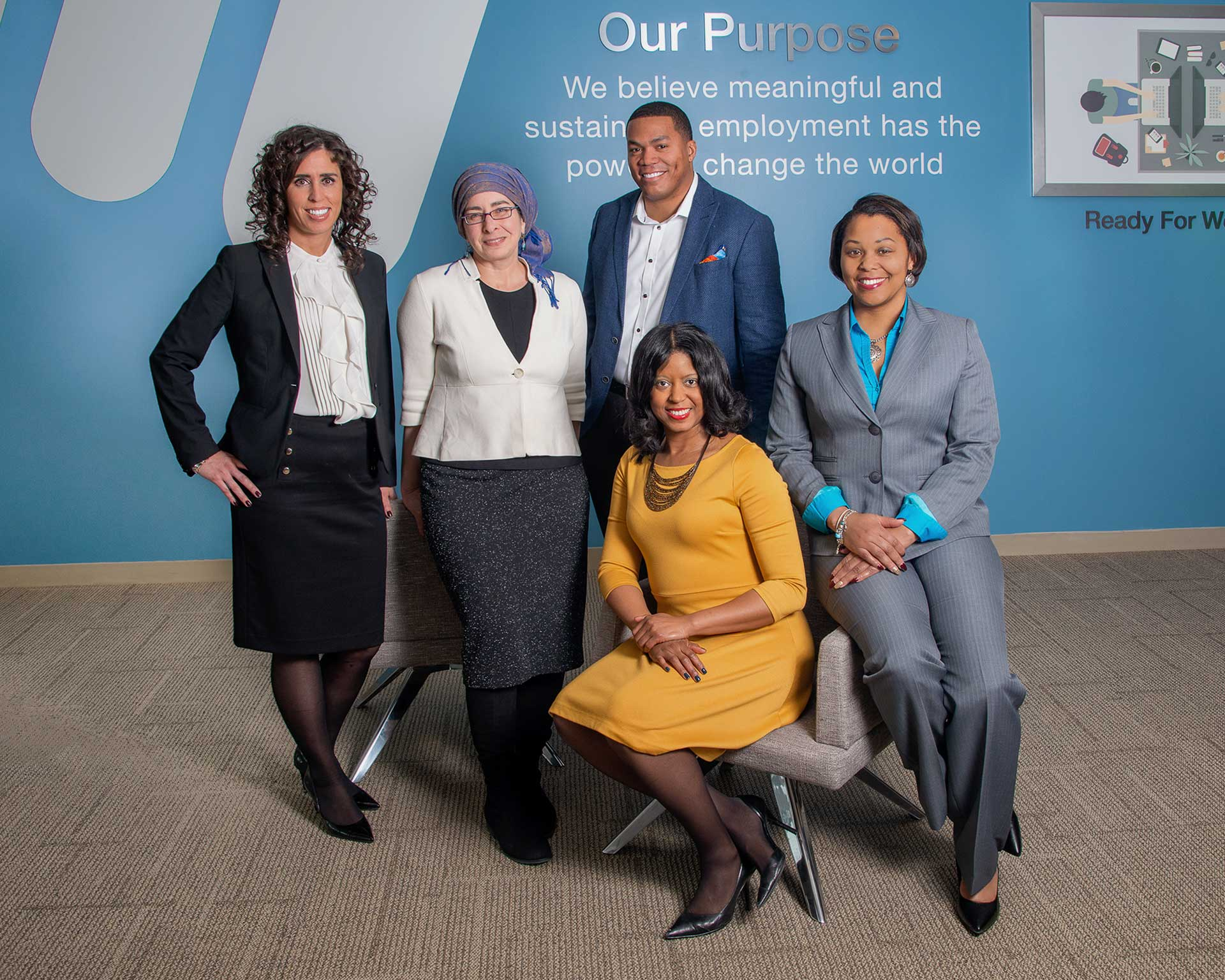 Image of a group of ManpowerGroup employees sitting in front of ManpowerGroup's Purpose wall