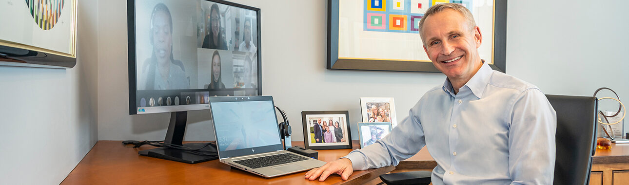 ManpowerGroup Chairman and CEO, Jonas Prising sitting at his desk, smiling while on a call with the ELT